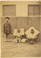 Prison Guard with Two Seated Prisoners in Cangues (Wooden Collars) Weighing about 16 Kilograms. Shanghai, China, 1874 WDL1922.png