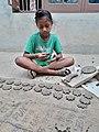 Punjabi child doing clay modelling.jpg