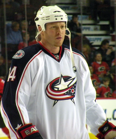 A Caucasian ice hockey player standing relaxed on the ice. He wears a white jersey with blue trim and a white helmet. He is looking forwards and holds his hockey stick with both hands across his torso.