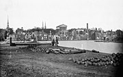 Wide view of a cityscape with evident destruction. Unused cannons and cannonballs litter the foreground, while a large Neoclassical building stands intact in the rear center.