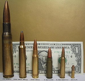 Ammunition - Various rifle cartridges compared to the height of a US$1 bill.