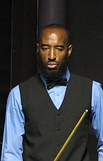 Rory McLeod is shown standing, holding a cue and looking down.