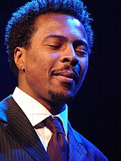 A man wearing a pin-striped suit with his eyes closed.