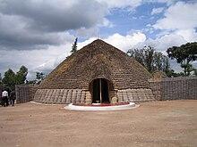 Foto de reĝpalaco en Nyanza, Ruando prezentanta ĉefenirejon, fronto kaj konusan tegmenton