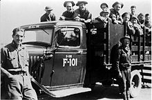 "Black and white image of a stakebed truck from the 1930s with two men standing in front and about a dozen men in the back. The truck is labeled ECW (Emergency Conservation Work, original name of the CCC) above the windshield, and ""S-118 F-101"" on the door."