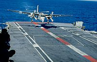 A large propeller-driven aircraft is moments away from landing on the flight deck of an aircraft carrier