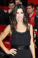 A portrait of Sandra Bullock wearing a black dress, with paparazzi standing in the background.