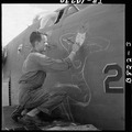 Sgt. J.S. Wilson, USA, painting a design of prow of a bomber based at Eniwetok. - NARA - 520724.tif