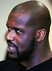 A bald, bearded black person looks toward the left, his mouth open.