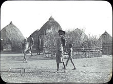 Early 20th-century village, with thatch-roofed huts and people walking