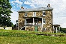 Two story stone house and porch with deciduous tree as seen from grassy yard