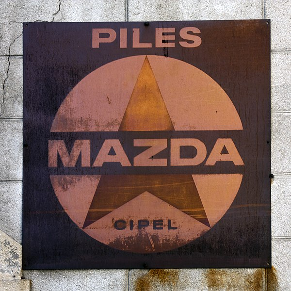 English:  Wall advertising for Mazda batteries, a  Compagnie Industrielle des Piles Électriques (CIPEL) production, first half of 20th century