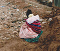 Squatting woman with child in Bolivia.jpg