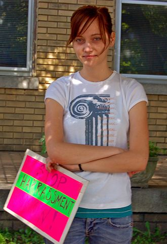Harassment - A woman standing in front of an abortion clinic holds an anti-harassment sign