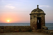 Old, somewhat decayed battlements, with a sunset in the background over the sea.