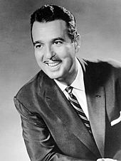 A smiling man with a thin mustache, wearing a suit and necktie
