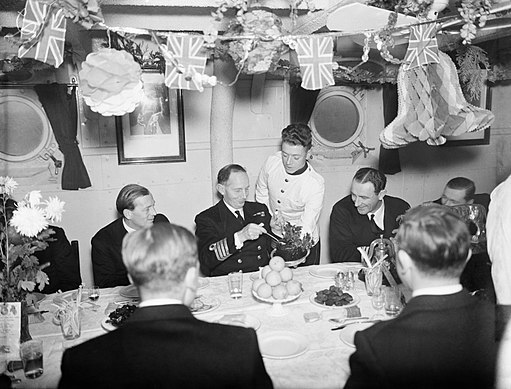 The Captain of HMS MALAYA helping himself to plum pudding during Christmas dinner at Scapa Flow, 25 December 1942. A13566
