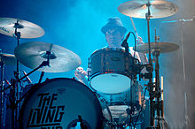 Strachan is mostly obscured by his drums. He wears a dark hat and stares ahead. His left hand has his drumstick high, while the right drumstick is low and over a cymbal.
