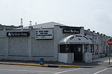 "A white brick building on a city street corner. On the side of the building, and on the entrance awning is ""The Stone Pony."""