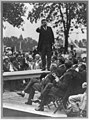 Theodore Roosevelt standing on table outdoors and making speech to men seated around him, right hand raised) - Smith Art Photography, Freeport, Ill LCCN91787238.jpg
