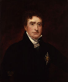 a portrait of a young man with dark hair and dark eyes. He is wearing a black jacket with some form of medal or badge pinned to the front, along with a raised collar and a small cravat.
