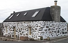 A small house with a black roof and a small chimney. The walls are constructed of stone and mortar; the former are undressed whilst the latter are painted white, creating a spotted effect.