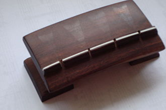 Jivari - Top view of a rosewood tambura bridge. Notice the marks left by the strings as the javari-maker assures that the contact-lines on the surface of the bridge are continuous and even. As a further test strings are pulled sideways and lengthwise in order to rub the bridge with the string, to better judge the quality of the surface, as unevenness in the surface shows clearly as a gap.