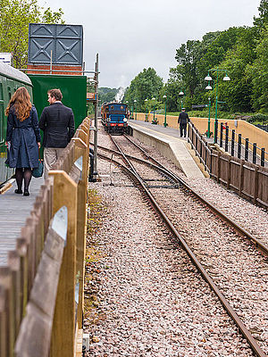East Grinstead railway station - A Bluebell Railway heritage train arrives into the Bluebell's East Grinstead station platform, during the railway's 2013 Edwardian weekend. The two people on the left are walking along the heritage line's Observation platform. To the right, beyond the second fence where the guard is, is located the connecting line to Network Rail
