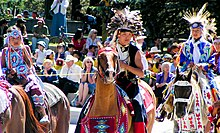 """Colour photograph of Tsuu T'ina children in traditional costume on horseback at a Stampede Parade in front of an audience"""