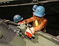 US Navy 030709-N-6803B-003 Boatswain's Mate 2nd Class Angela Kerr assigned to the U.S. Navy Cargo Handling and Port Group (NAVCHAPGRU) lashes equipment to the deck of USNS Charlton (T-AKR 314).jpg