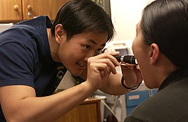US Navy 040113-N-4614W-005 Capt. Wan Mun Chin examines a patient suffering from a sore throat and high fever.jpg