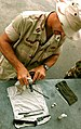 US Navy 040808-N-3750S-005 Lt. Jim Golden assigned to Naval Mobile Construction Battalion Two Three (NMCB-23) disassembles, cleans and reassembles his 9mm pistol as part of a two day weapons qualification course.jpg