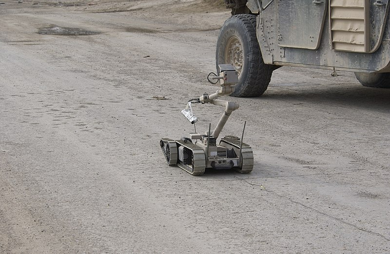 i-Robot carries a stick of C4 plastic explosives down the street to an alleged improvised explosive device