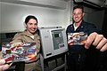 US Navy 050215-N-3228G-002 Disbursing Officer, Lt.j.g. Elizabeth Williams, left, and Disbursing Clerk 1st Class Michael Brett, display their Navy Cash Cards in front of a K80 terminal aboard the guided missile cruiser USS Lake.jpg