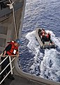US Navy 060311-N-1045B-123 Sailors pull up lines after lowering a Rigid Hull Inflatable Boat (RHIB) into the sea during a man overboard drill.jpg