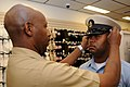 US Navy 080825-N-9758L-026 Chief Information Specialist Technician Dwayne Peterson fits a combination cover on the head of Religious Program Specialist 1st Class Tshombe Harris.jpg