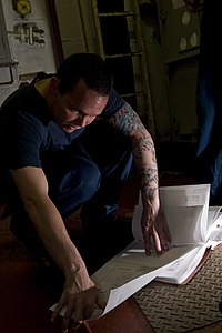 US Navy 120105-N-TZ605-211 Electrician's Mate 3rd Class Joshua Scammell eviews electrical schematics while troubleshooting an air conditioning powe.jpg