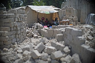 Bangui - A family uses tarpaulins from a refugee camp to get shelter from the sun, with bricks for rebuilding their homes all around them in the PK5 neighbourhood.