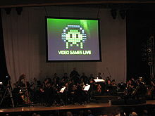 A photograph of an orchestra on a dimly lit stage. Above the group is a projection screen with a black, white, and green image of pixel art. The pixel art is an oval object wearing headphones with eyes and four tentacles. Below the pixel art is the phrase