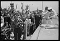 Vice President Lyndon B. Johnson, standing in a car as Secret Service agent stands by, saying goodbye to crowds at airport, before leaving Taipei, Formosa LCCN2018654382.jpg