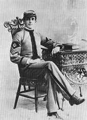 A ornate chair and a table with a book on it. A man sits in the chair, wearing an American Civil War style peaked cap. On his sleeves he wears three stripes pointed down with a lozenge of a First Sergeant.