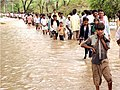 Villagers walking towards dry ground on a flooded area at Khera village near Ahmedabad in Gujarat on July 4, 2005.jpg