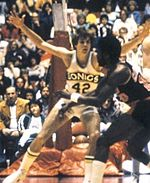 "A man wearing a white jersey with the word ""SONICS"" and number ""42"" written on the front spreads his arms in a defensive position."