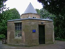 Small five-side stone building. The only floor contains a door and window and is topped by a short, pointed tower.