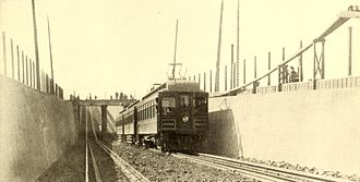 "Key System - A Key System train in Emeryville, 1909, heading west to the Mole, entering the underpass (""subway"") under the mainline of the Southern Pacific under construction."