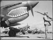 "A Chinese soldier guards a line of American P-40 fighter planes, painted with the shark-face emblem of the ""Flying... - NARA - 535531"
