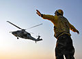 A U.S. Sailor signals to an MH-60 Seahawk helicopter pilot assigned to Helicopter Sea Combat Squadron (HSC) 2 during flight operations aboard amphibious transport dock ship USS San Antonio (LPD 17) in 110610-N-VL218-204.jpg