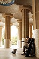 A musician playing among columns of Sala Hipóstila, Park Güell ( UNESCO World Heritage Site), hill of El Carmel, Gràcia (district), Barcelona, Catalonia, Spain.jpg