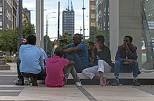 A group of black African men sitting or squatting on a low bench next to a glass wall in a large city square. In the rear can be seen a street with a tall rectilinear skyscraper
