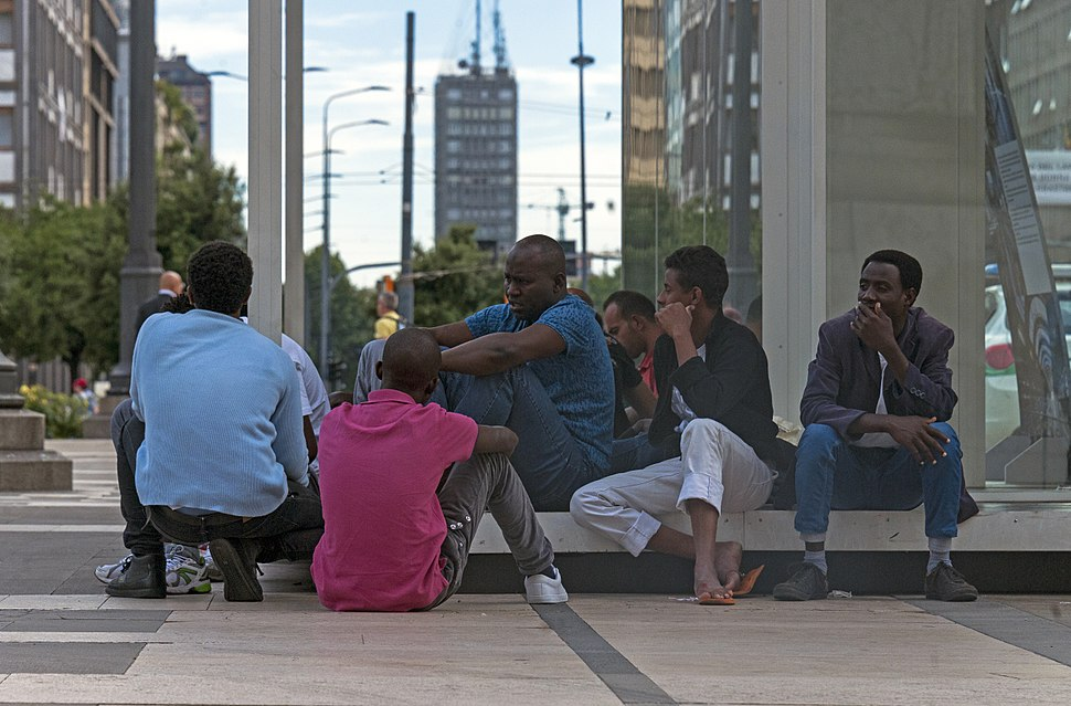 African men sitting on the Piazza duca d'Aosta, Milan, in evening